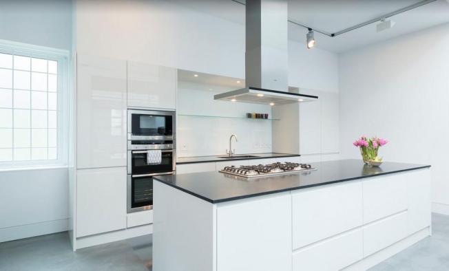 Uma cozinha branca com uma grande ilha e a sala de jantar formam um grande salão!